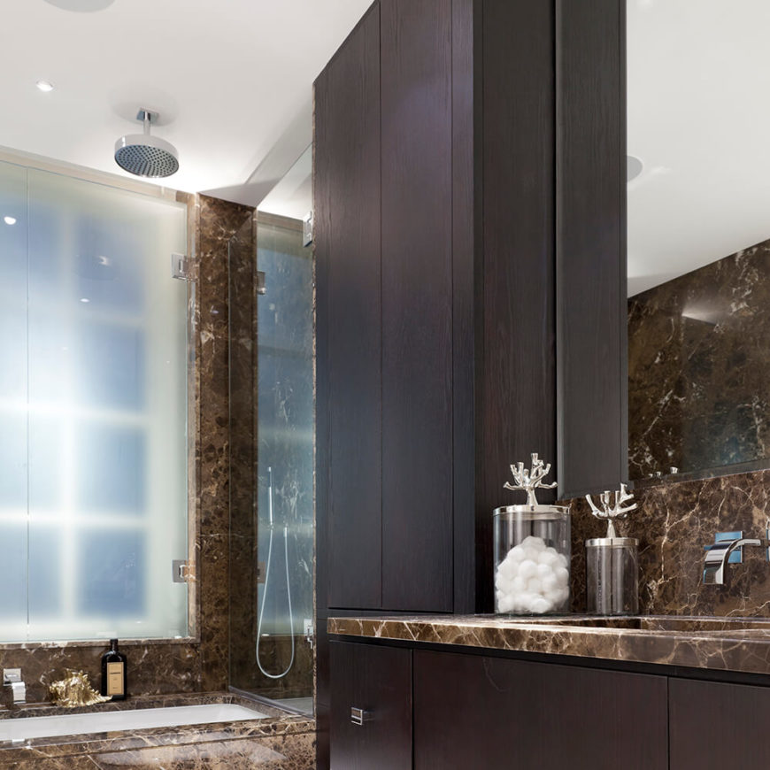 This bathroom boasts a darker color palette, with deep marble tones and dark stained wood cabinetry. The soaking tub, countertop, and even wall are flush with the rich marble, making for a luxurious appointment.