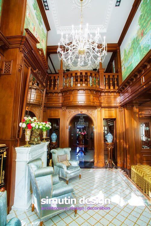 A large balcony overlooks the great room, along with a massive chandelier. The top of the great room is filled with pastoral murals in soft greens. To the right of the room is a golden upholstered chaise.