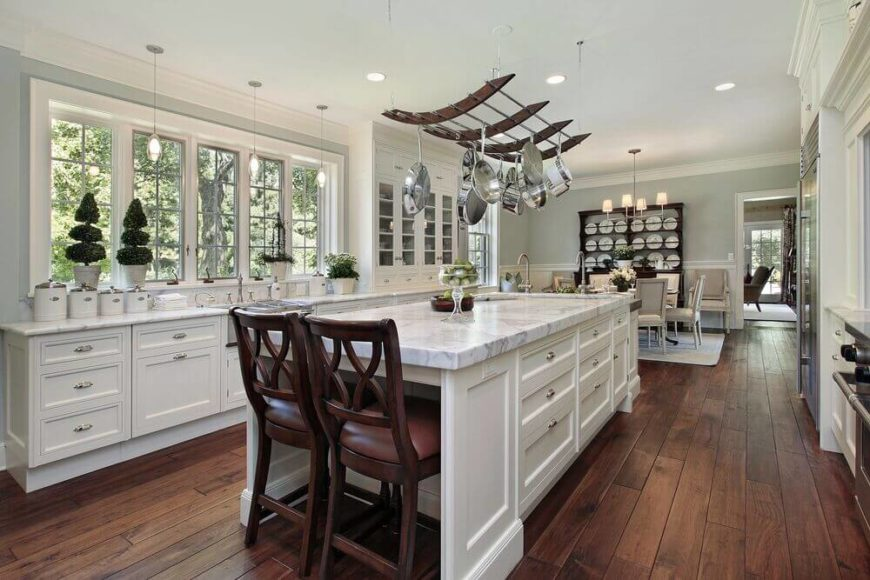 Lovely Luxurious Modern Kitchen With Elegant Pot Rack Hanging Over The Marble  Topped Island.