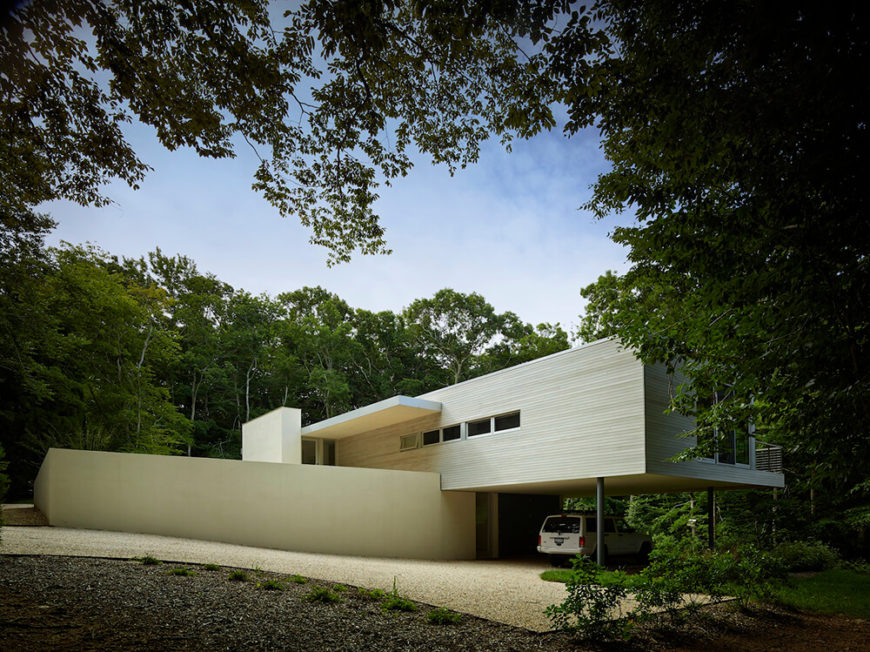 The driveway slopes down beneath the right wing of the home, which conveniently provides parking shelter. The front of the home is an exercise in minimalism, with broad slabs of white and few windows dotting a monolithic appearance.