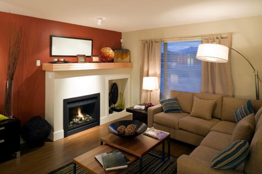 Or add an accent wall in a warm tone to add a cozy feeling. Adding a dusky red to the wall behind a fireplace doubles the warmth of this room.