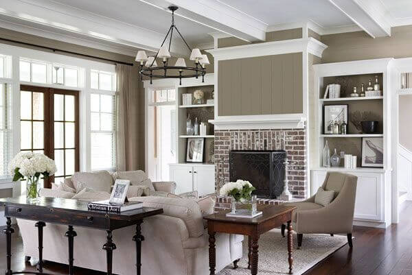 While taupe is still a cooler color, it brings out the warmth in the brick fireplace and in the wood floor, warming the room.