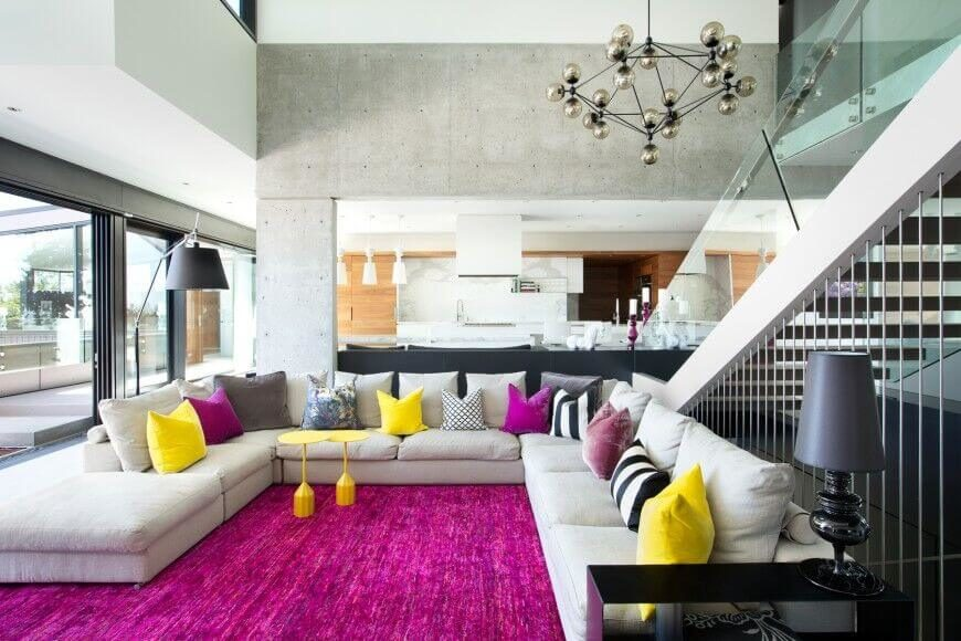 Bright sunshine yellow and berry purple pillows accent the enormous beige sectional sofa, along with a matching textured area rug.
