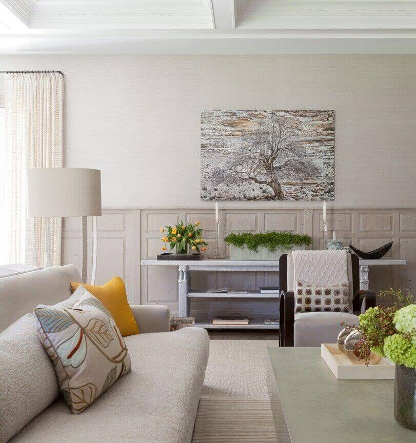Floral arrangements bring richer, more lively colors to this soft beige beach home's living room.