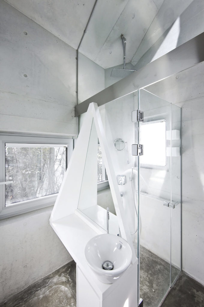 The bathroom sports more intricately shaped white framing elements, as well as a walk-in shower with rainfall head.