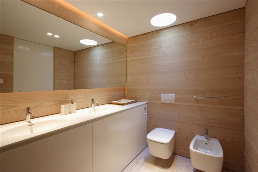 The minimal design of this bathroom is lovely in its simplicity. The white accents allow the beautiful grain in the natural wood to showcase while the large mirror helps to make the narrow space seem even larger.