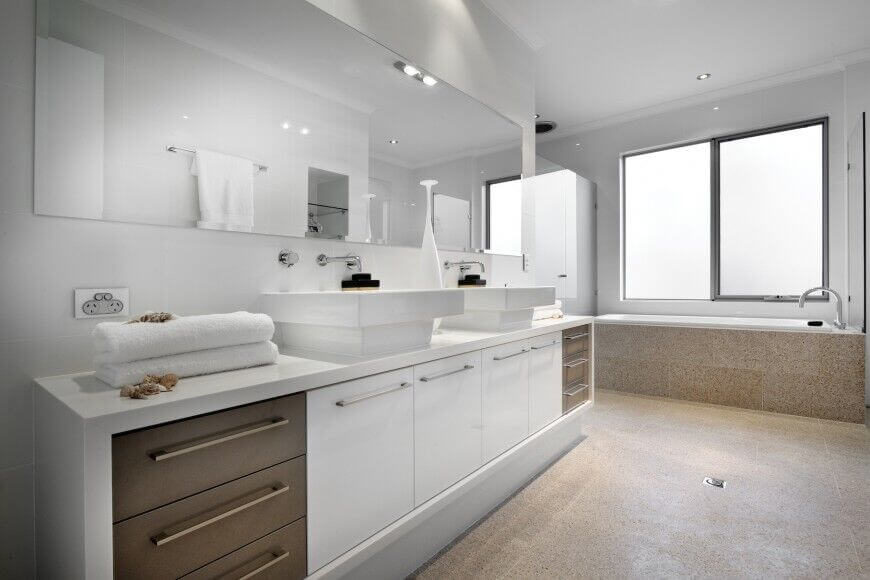Earthy, warm tones balance out the cool white of this bathroom. Large windows let in plenty of natural light and brighten up the white even more. The tan speckled floor mimics a sandy beach without the hassle of sand.