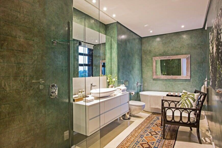 Jade-colored walls are the highlight of this lovely bathroom. The white cabinets and accents stand out against the jewel tone walls while also helping to reflect their true color even more. The bold colors of the rug create visual interest and give the floor some extra attention.