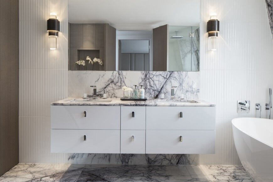 The highlight of this bathroom is the gorgeous veined marble across the floor and up into the backsplash of the floating vanity. The white textured wall breaking up the space is an added bonus and helps to show off the marble even more.