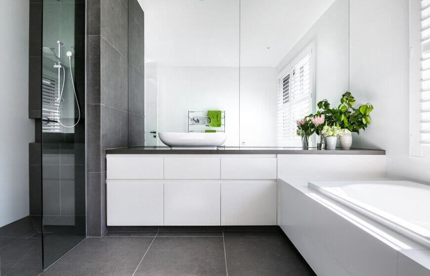 Brilliant pops of green break up this monochromatic bathroom design. Sleek, streamlined edges create a clean, minimalist feel in this room.