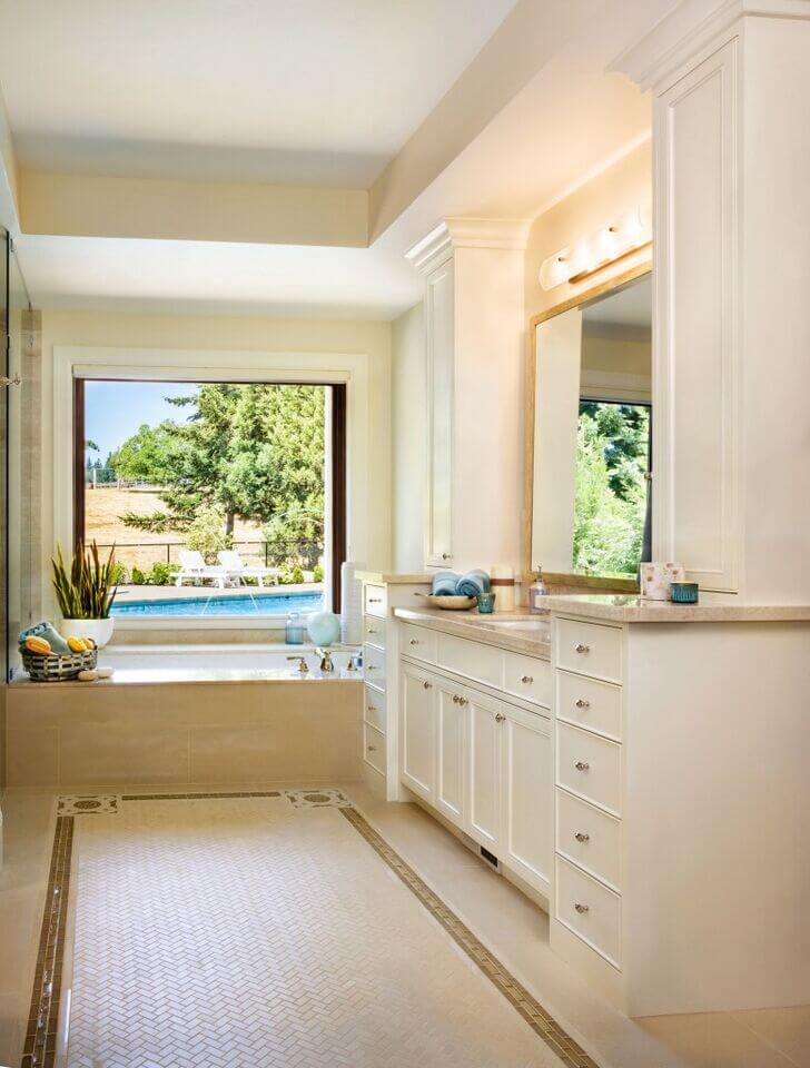 Bright blue accents bring the colors of the pool in the background into this pale colored bathroom, livening up the space considerably. Gold accents in the floor tiles and around the mirror bring a touch of luxury.