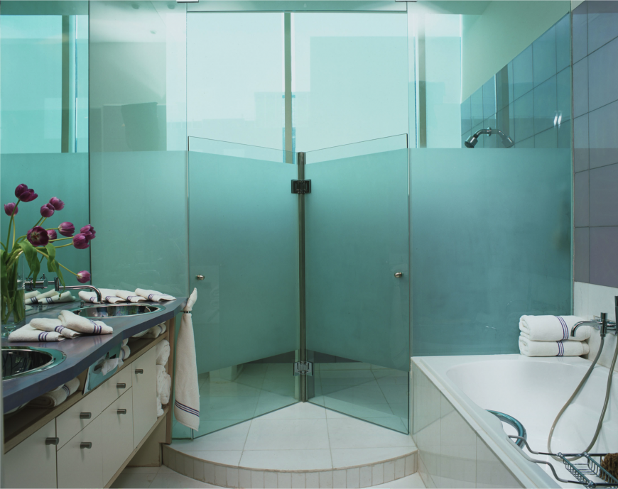 Frosted glass brings in plenty of color to this room. Dark purple counters and muted wall tiles contrast this bright use of color and add another layer to the palette of this bathroom.