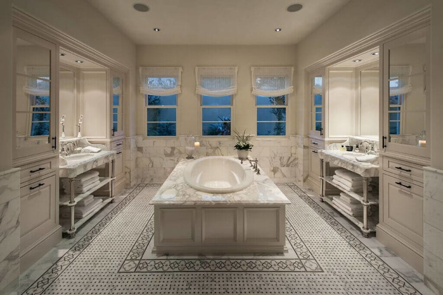 This striking bathroom creates a rich, calming place to unwind. The large tub in the center of the room shows off the beautiful marble used throughout the bathroom. Mirrored cabinets help to expand the space and the patterned floor helps to ground the airy look.