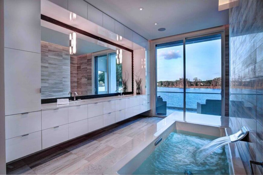 A wall of white cabinets offers up plenty of storage in this lovely bathroom. The stunning tub mimics that body of water outside the house and brings its calming display into the house.