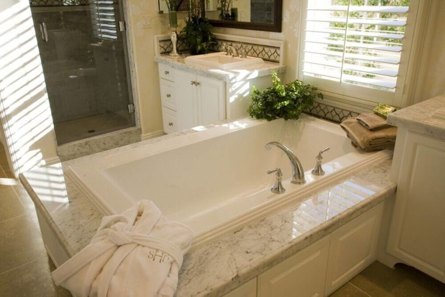 The gorgeous tub, flanked by white cabinets, is a beautiful centerpiece to this bathroom.