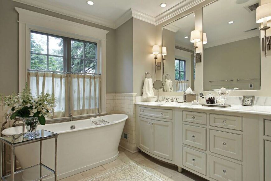 The subtle, muted color scheme of this bathroom offers this room a calming and peaceful atmosphere. White cabinetry and trim complement the white tub and marble countertops.