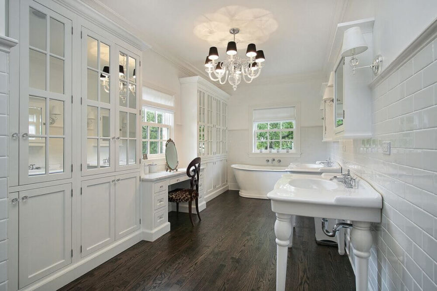 This stunning use of white shows off the gorgeous wood floor in this bathroom. Delicate details - like the chandelier, turned-wood legs of the sinks, and mirrored cabinet insets - make the space interesting and stand out even when all in white.