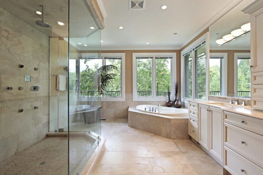 Neutral tones in this bathroom work to highlight the greenery of the surrounding landscaping outside the large windows. Contemporary white cabinetry both blends in and stands out against the creamy hues of the floor.
