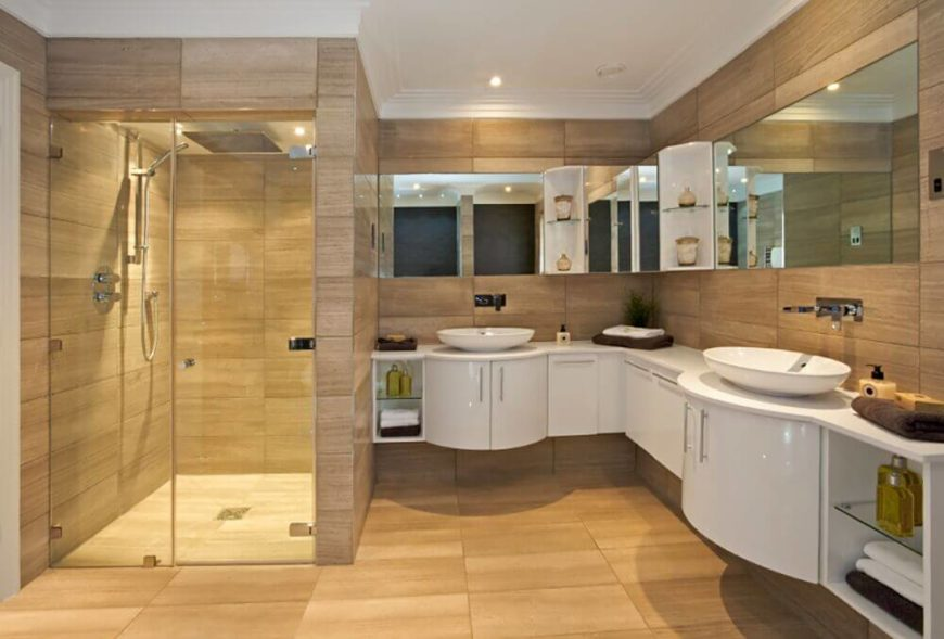 Modern white cabinets highlight the texture of the tan walls in this bathroom. The graceful curves of the sinks, corner shelves, and cabinets contrast the sharp angles of the wall tiles and shower.