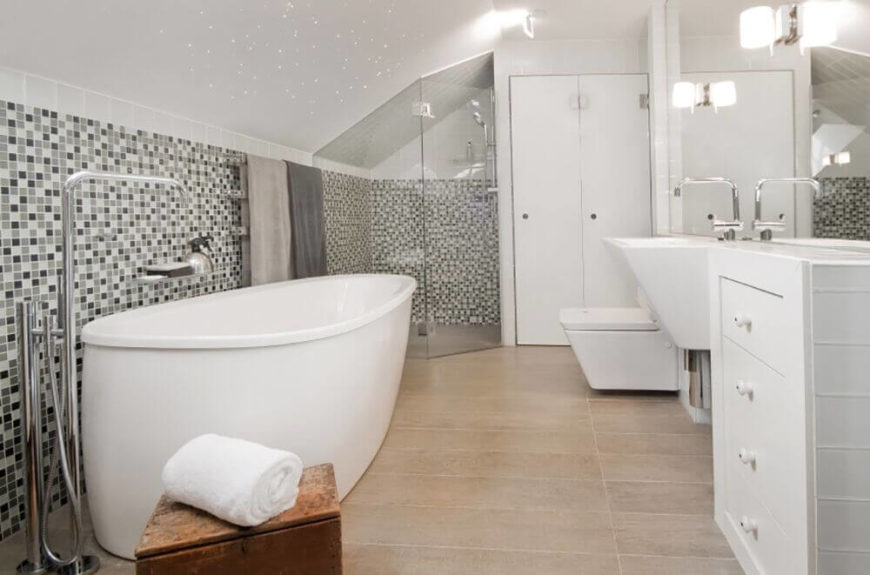 This uniquely shaped tub pops against the mosaic tiled wall. Similarly, the shower, sink, and toilet all feature uncommonly seen shapes and angles when it comes to bathroom fixtures. The neutral floor color allows the rest of the room to stand out.