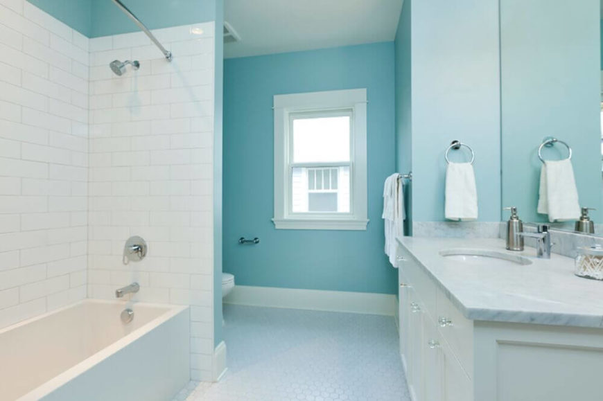 Another bright blue wall creates a calming space in this room, balancing the white accents nicely. Pale and bright colors need to be used to ensure the room reflected plenty of light.