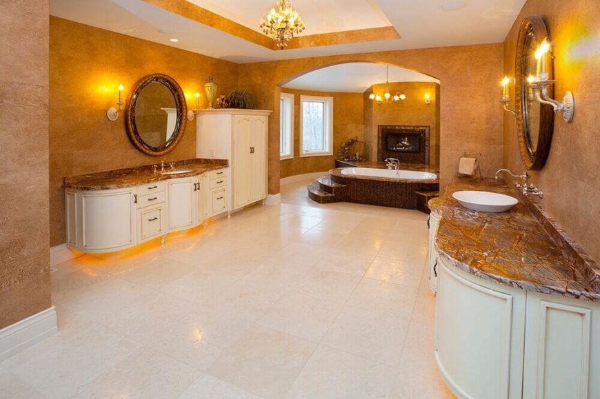 Opulence is the word that comes to mind when looking at this golden bathroom. Amber light reflects off the iridescent veins in the counters and warmly textured walls double the glow of the lights. Dark marble around the tub creates a balance of light and dark when viewed against the white of the floor and cabinets.