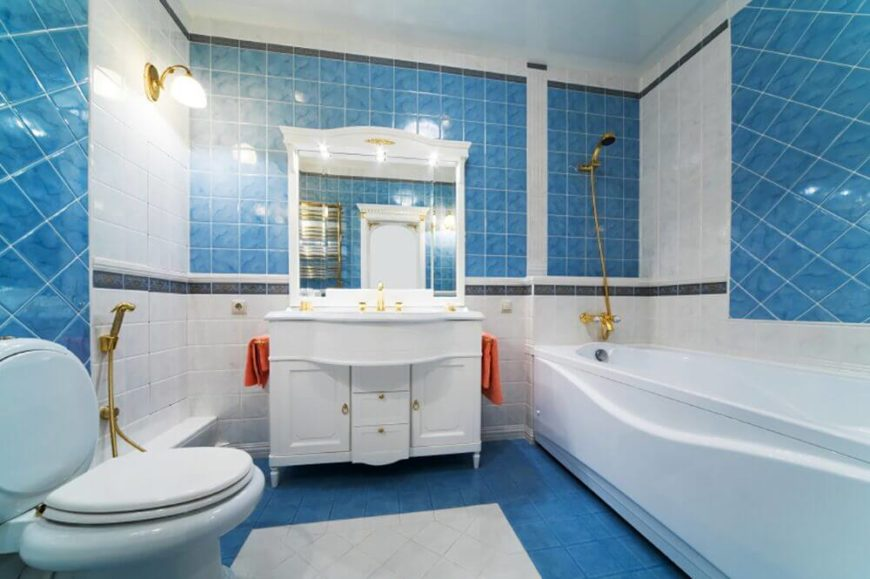 Bright blue seems to be a common theme in bathrooms. This one utilizes bold orange accents and touches of bright gold in the fixtures. The subtle texture of the blue tiling keeps the blue from being flat or overwhelming.