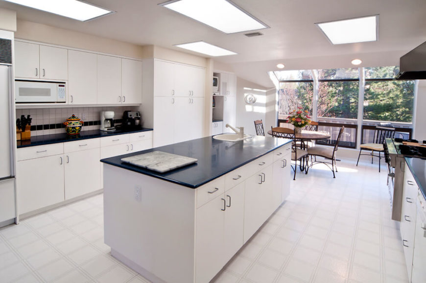 Here is an example of larger recessed lighting, filling this whole space with bright, spacious light. Covering a larger area, it reflects off the white surfaces of this airy kitchen and fills the room with more light.