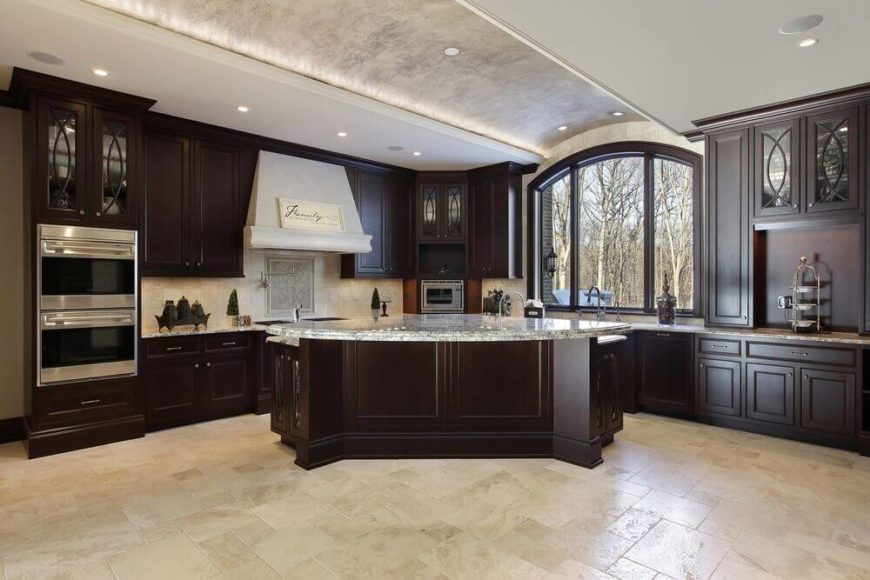 Recessed lighting along the inner edge of the ceiling arch works to highlight the unique feature of this kitchen. It offers a soft ambient glow to the room while the can lights illuminate the rest of the room.