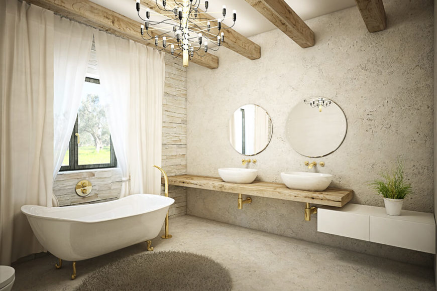 The master bathroom is a large, luxurious space appointed with gold plumbing and a floating dual vanity in natural wood, with a pair of vessel sinks. The claw foot tub stands next to a window and beneath a modern chandelier.