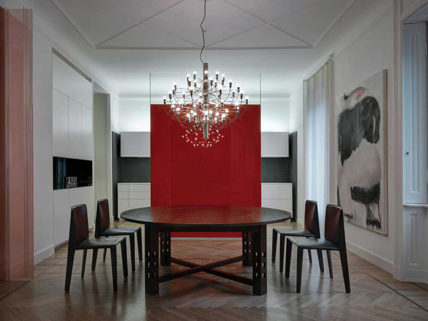 The dining room features a beautiful, solid, dark wood round table with matching modern chairs and the bold red accent wall. The striking chandelier over the table is a gorgeous addition to the room and the herringbone floors are used throughout the apartment.