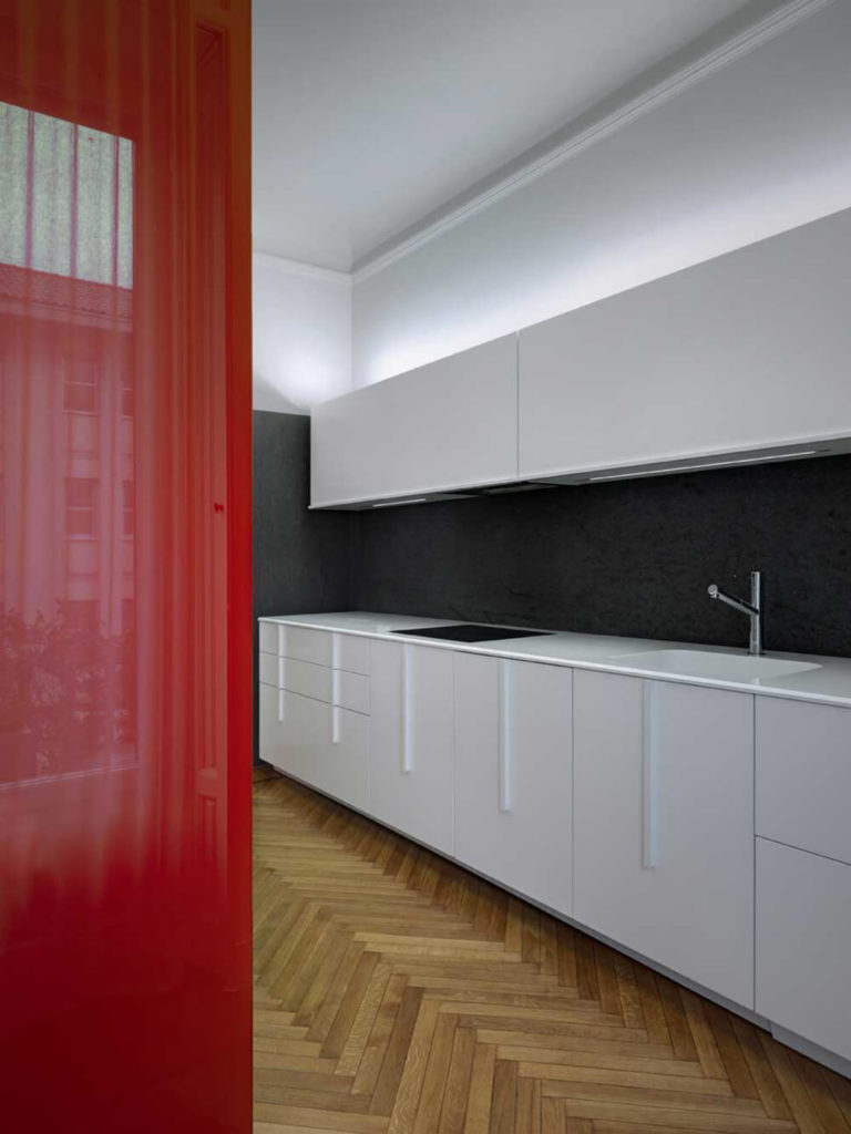 Behind the red wall is the sleek, streamlined modern kitchen. Soft perimeter lighting above the cabinets illuminates the high ceiling and fills the narrow space with an ambient light. A textured black backsplash creates lovely contrast against the white cabinetry.
