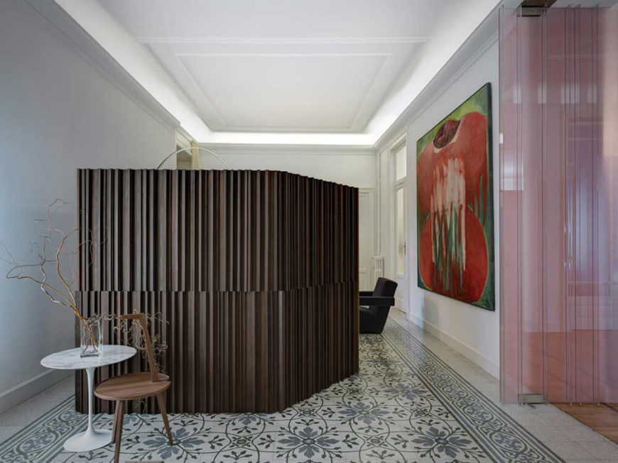 To the left of the dining room, through the transparent pink doors is the office and sitting room. A ridged wooden screen creates a place of privacy from the rest of the room while a patterned tile floor creates a bit of change from the rest of the home.