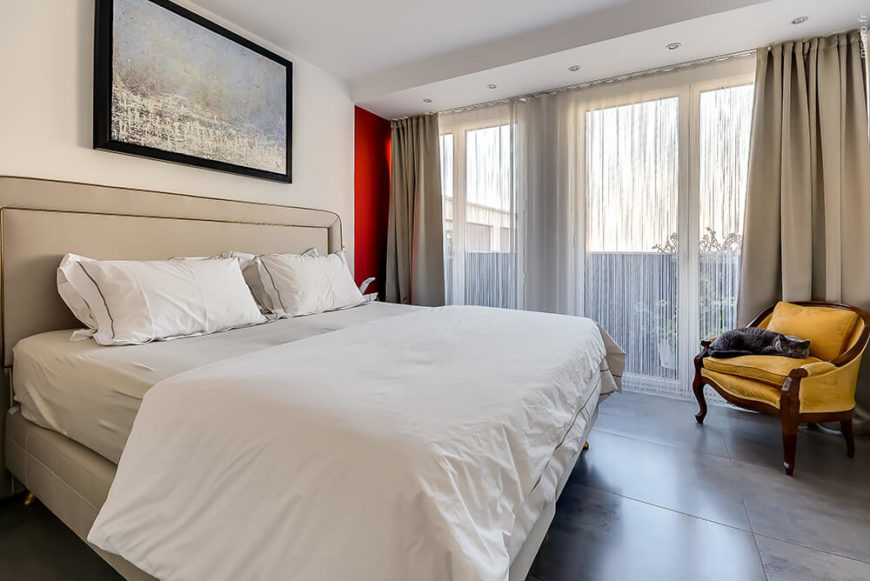 The master bedroom is more subtle than the rest of the house for a calming and tranquil atmosphere. A soft canary yellow chair brings some color as well as the doorway to the bedroom.