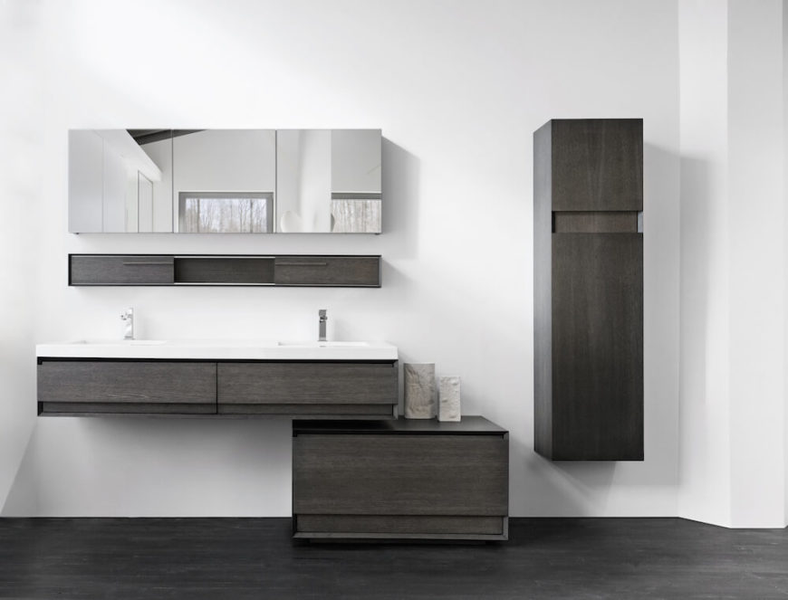 This smaller version of the vanity features the same two sinks, but with only the shallow drawers below the sink, and a detached lower drawer slightly to the right. A wall linen cabinet finishes off the furniture to the right of the sink. Above the sink is another slim set of cabinets with a three-paneled mirrored cabinet above it.