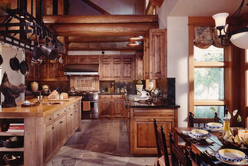 Keeping with the rustic theme of this lodge, the natural finish of these cabinets is on point. When coupled with the dark granite counters and contrasted by the light wood of the island they stand out wonderfully. The heavy duty pot rack suspended from the ceiling is a lovely touch.