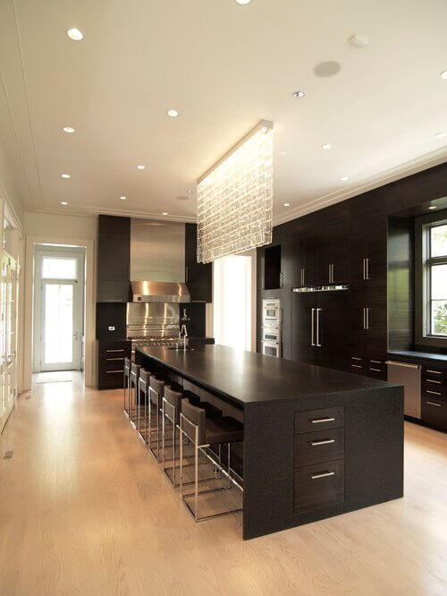This gorgeous kitchen just oozes sophistication and class. The dark wood of the cabinets against the pale colors of the room make a striking design. Stainless steel accents and the marvelous lighting feature over the island finish the room off well.