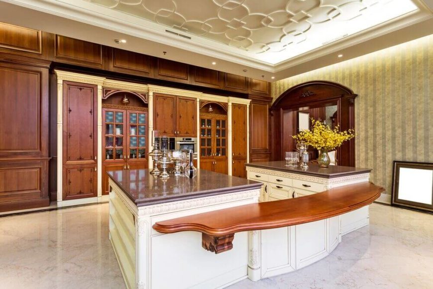 Dark cabinets fronts and woodwork are balanced by a combination of white cabinets, marble floor, and pale walls. A lovely wood bar that matches the cabinets connects the two islands into one 'U' shaped island. This gives the room a massive, open feel. The recessed ceiling boasts recessed lighting and a lovely geometric pattern.