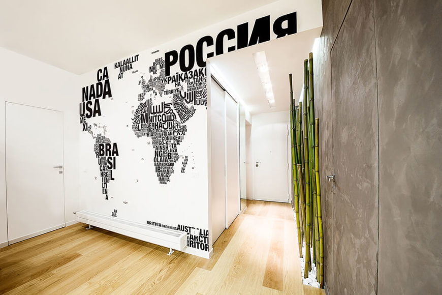 Pulling back to reveal the wide expanse of the living room, we can take in a unique artist's rendition of the world map. Each country is represented by its name in lettering that corresponds with its respective size. This bold decal directly nods to the owners' adventurous nature.