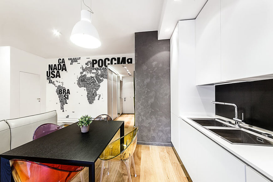 The kitchen sports sleek white cabinetry from floor to ceiling, bisected by a jet black backsplash at right. The dining table, in all black wood, is surrounded by a quartet of colored acrylic chairs.