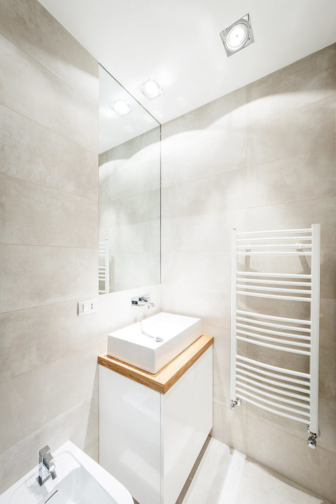 This smaller bathroom offers a wealth of utility and minimalist grace. A white drying rack hangs on the wall beside the natural wood topped vanity with rectangular vessel sink.