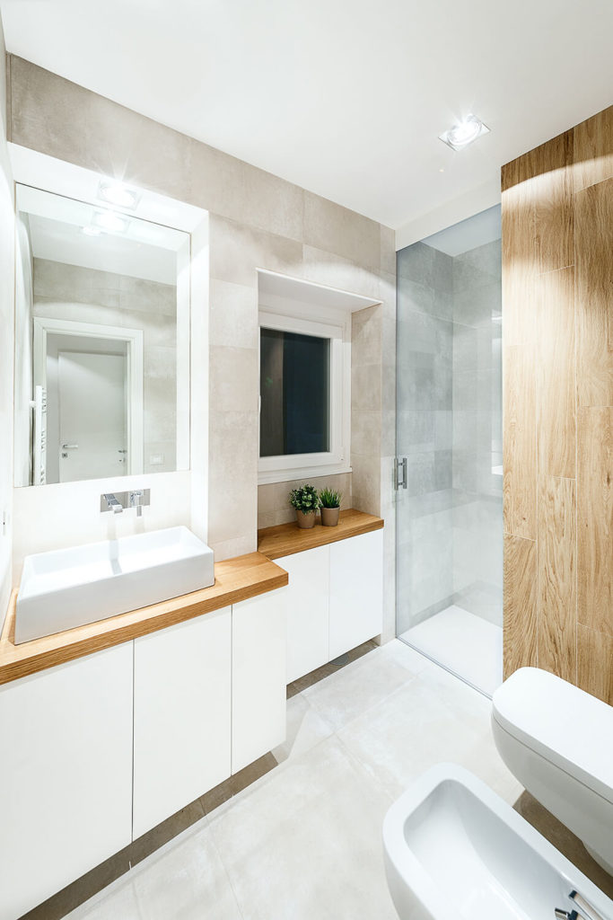 The master bath sports a similar mixture of glossy whites, light grey concrete, and rich natural wood. The vanity once again boasts a rectangular vessel sink over hardwood countertop.