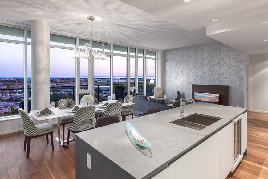 Moving into the kitchen itself, we grasp how large the grey-topped island is, replete with wine storage and built-in full size sink. The island helps define the kitchen within the larger open space. From here we can see the city expanding to the horizon.