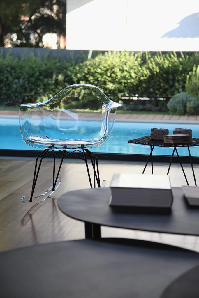 The creative acrylic rocking chairs in the living room create both function and a fun visual to the room that allows the exterior courtyard and pool to be the focal point of the area.