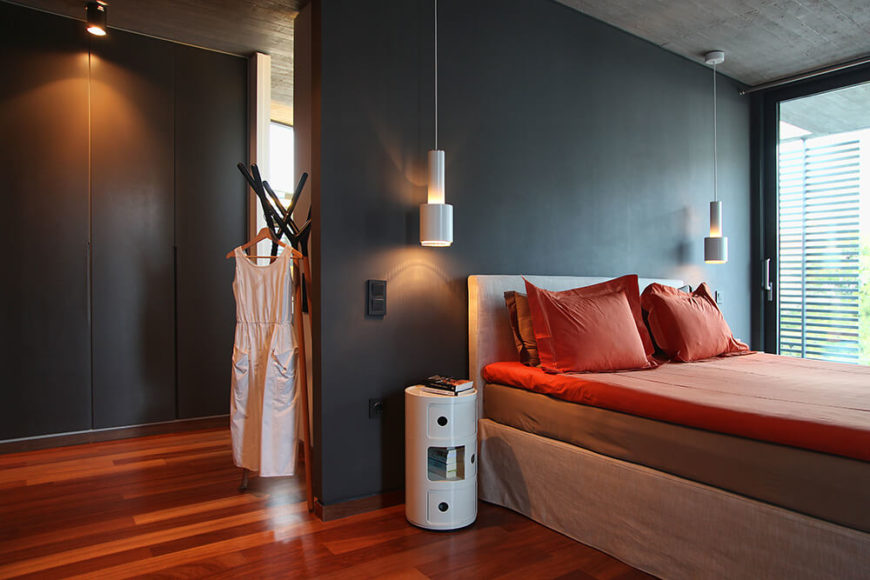 Pictured here in the master bedroom of the second floor sleeping quarters. The wood floor from the living room is used throughout this floor and it complemented by the warm hues of the bed linens. Black walls and while accents allow this bright warm colors to pop.