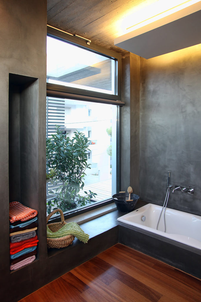 The attached bathroom to the master suite looks out over the garden area of the balcony and offers privacy to the occupants. A bathtub and small bench a featured in this particular corner.