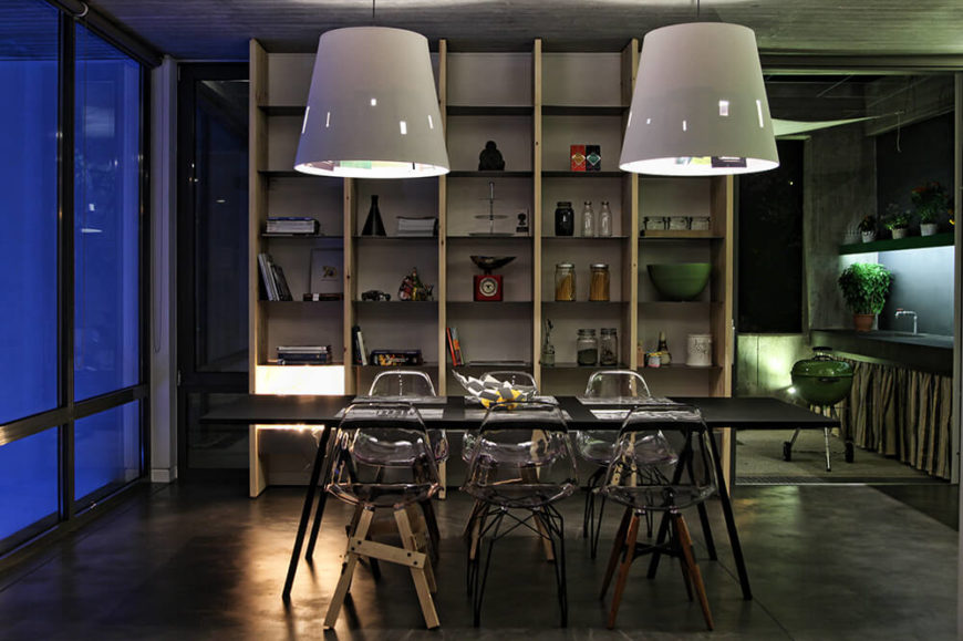 The acrylic chairs make an appearance again in the dining area, this time with mismatched bases. From this angle you can see the wall of shelves built into the space and filled with plenty of storage areas.