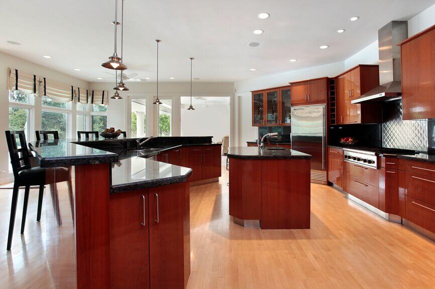 This White Kitchen Features Light Honey Hardwood Flooring And A Near Matching Island Countertop. photo - 3