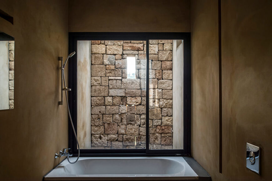 This bath is featured on the lower level of this home, with a view of the retaining wall that wraps around the exterior. The dark colored walls are textured and create a natural feel in this small space.