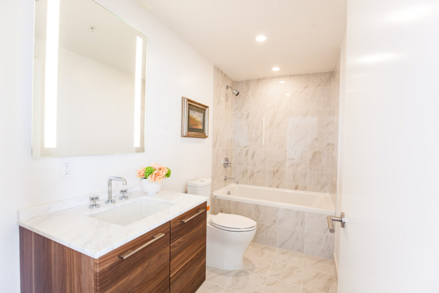 Here we see one of the bathrooms, awash in marble tile and white walls. The marble topped island features natural wood cabinetry as a bold textural counterpoint.